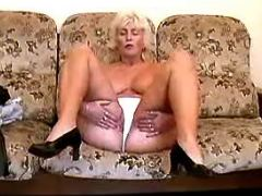 Chesty old lady with juicy pussy relaxing on sofa