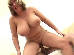 Chesty mature plays with hard cock and rides him